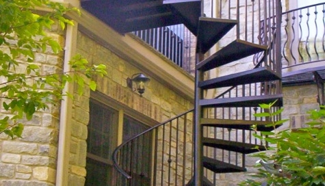 custom wrought iron spiral staircase connected to porch railing from finelli architectural iron and stairs